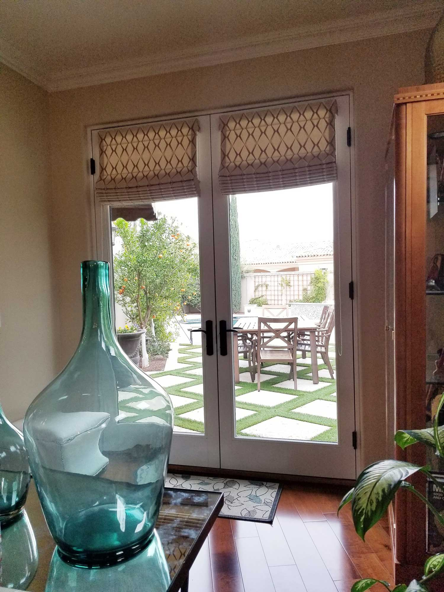 window from living space opening into a patio with dining table and chairs