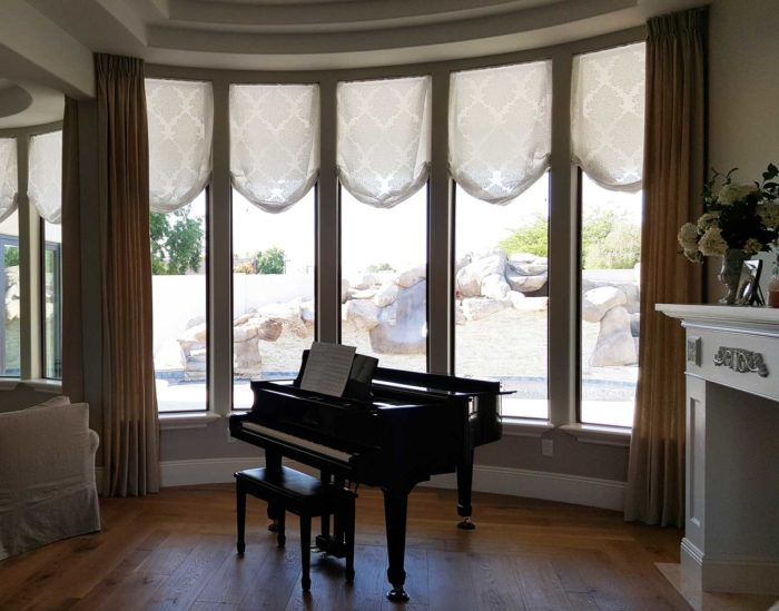 living room corner with piano and full, circular window panels