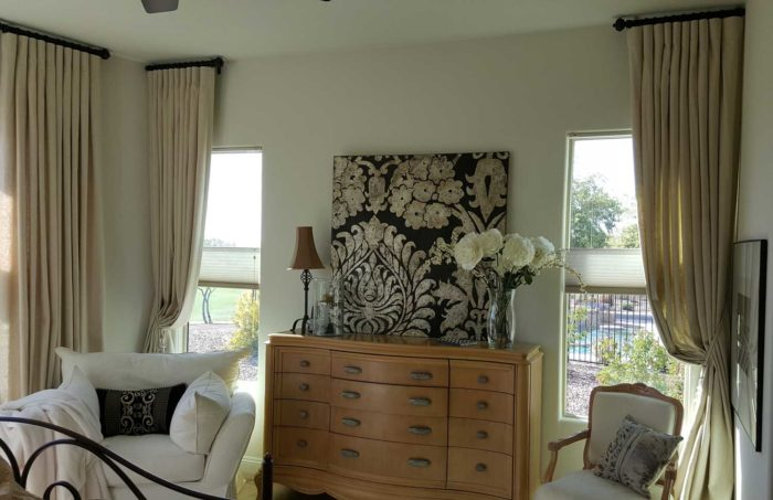 living space with chest-of-drawers between two curtained windows